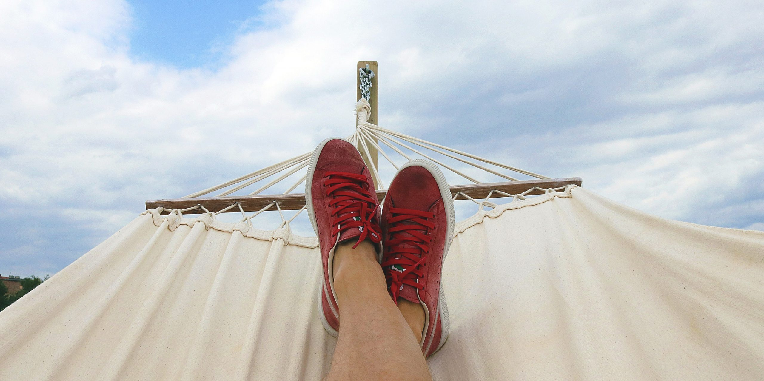 person relaxed on hammock only showing shoes